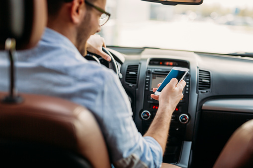 istock Man looking at mobile phone while driving 1098270098