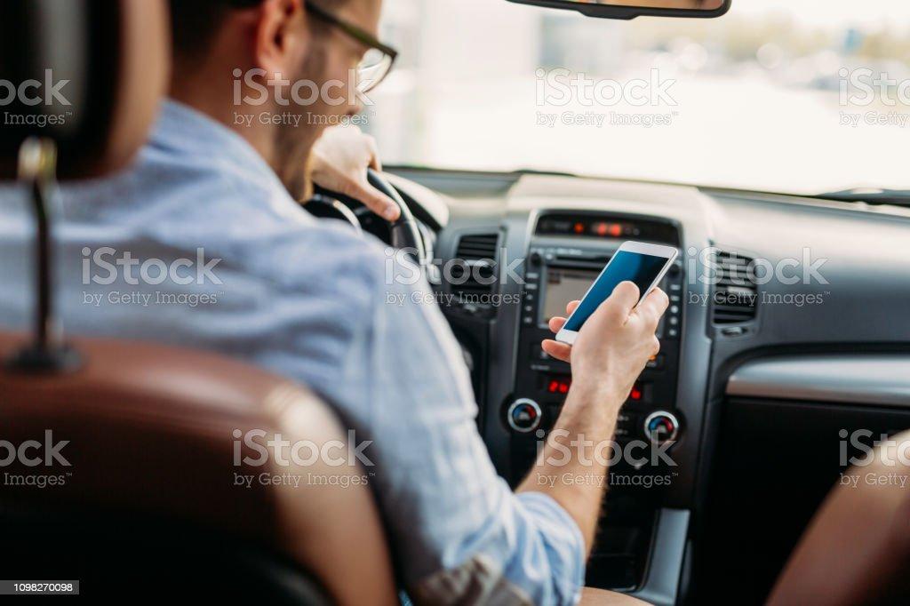 Mann am Handy während der Fahrt – Foto