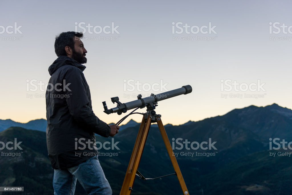 Man looking at mountain peaks near telescope in summer evening at sunset on mountain outdoor stock photo