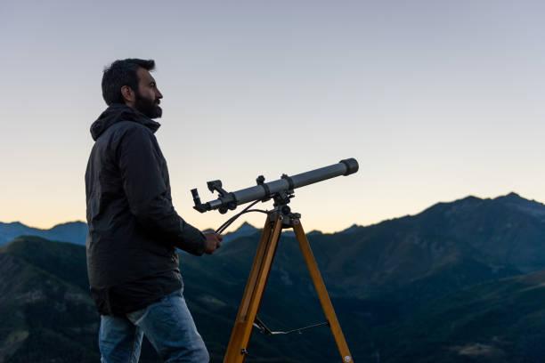 homme regardant pics montagneux près de télescope en soirée d'été au coucher du soleil sur la montagne en plein air - astronomie photos et images de collection