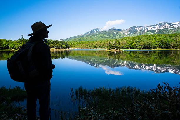 Man looking at Mountain reflection in Lake Yonko, Hokkaido, Japan stock photo