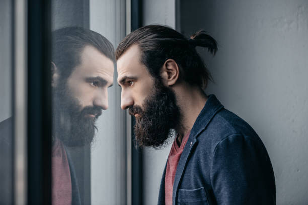 man looking at reflection in glass thoughtful bearded man looking at reflection in glass man bun stock pictures, royalty-free photos & images