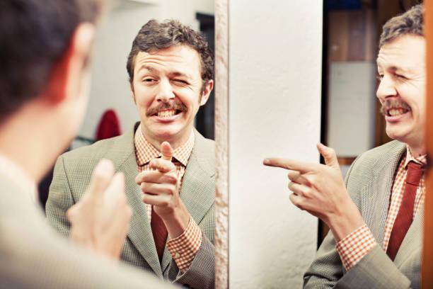 homem olhando no reflexo em um espelho - orgulho - fotografias e filmes do acervo