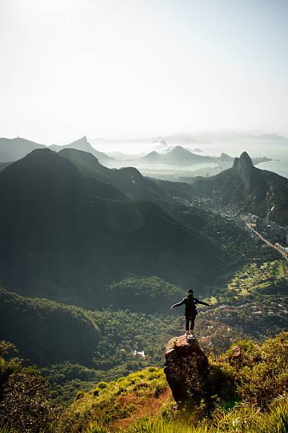 Man looking at Rio de Janeiro from above Man looking at Rio de Janeiro from above, shot from Pedra da Gavea. lagoa rio de janeiro stock pictures, royalty-free photos & images