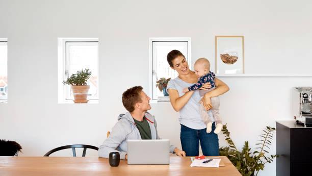 Mann, der Sohn anschaut, der von einer Frau zu Hause getragen wird – Foto