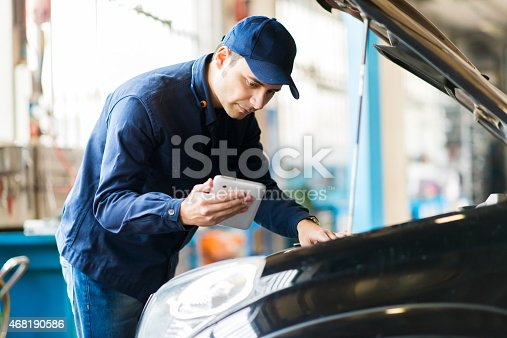 istock Man looking at tablet while trying to fix his car 468190586