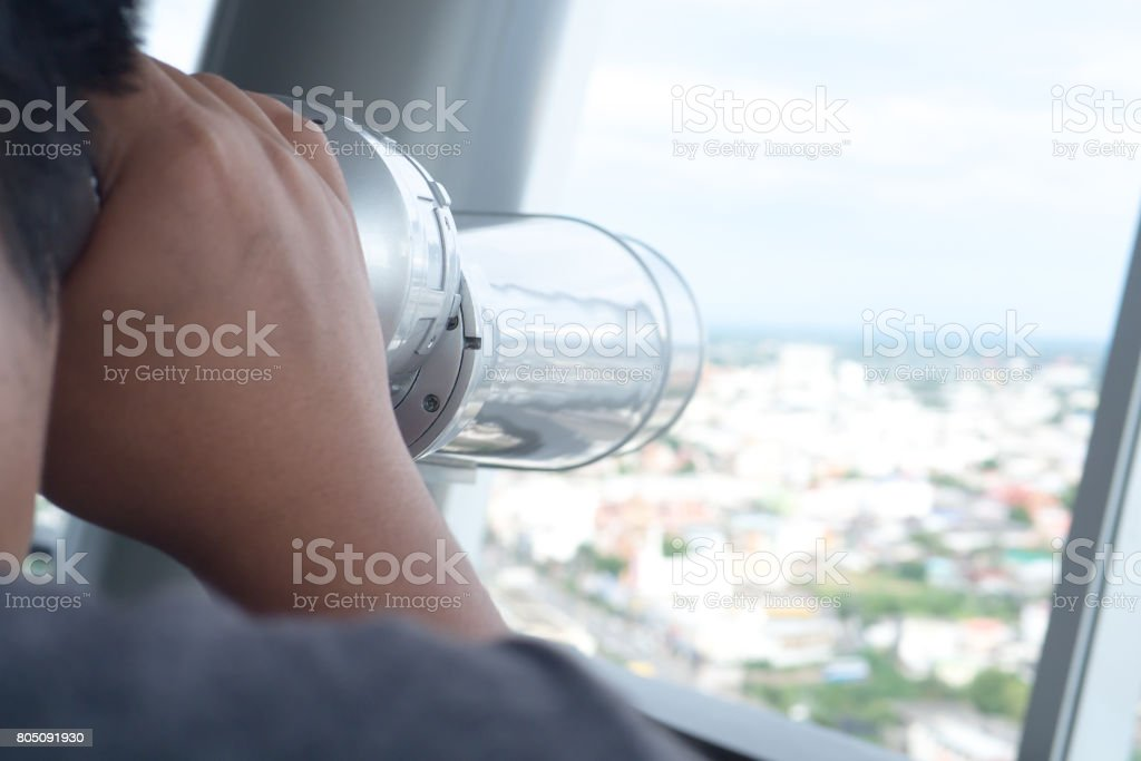 Man looking at the binocular to the view at the height building stock photo