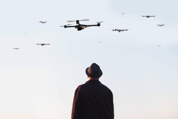 Hombre mirando el cielo lleno de drones - foto de stock