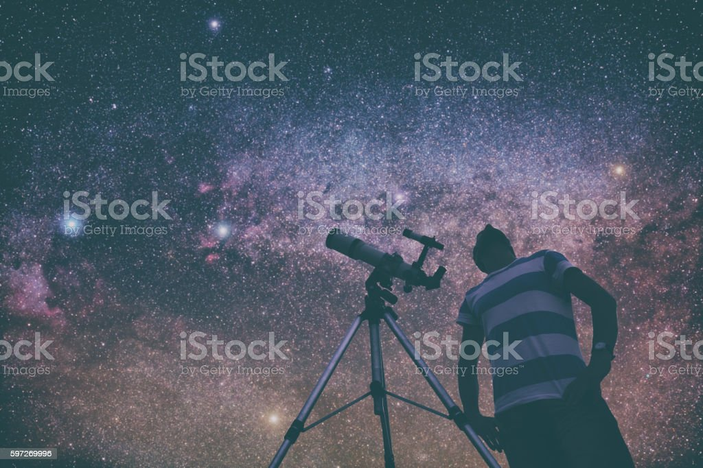 Man looking at the stars with telescope beside him. Lizenzfreies stock-foto