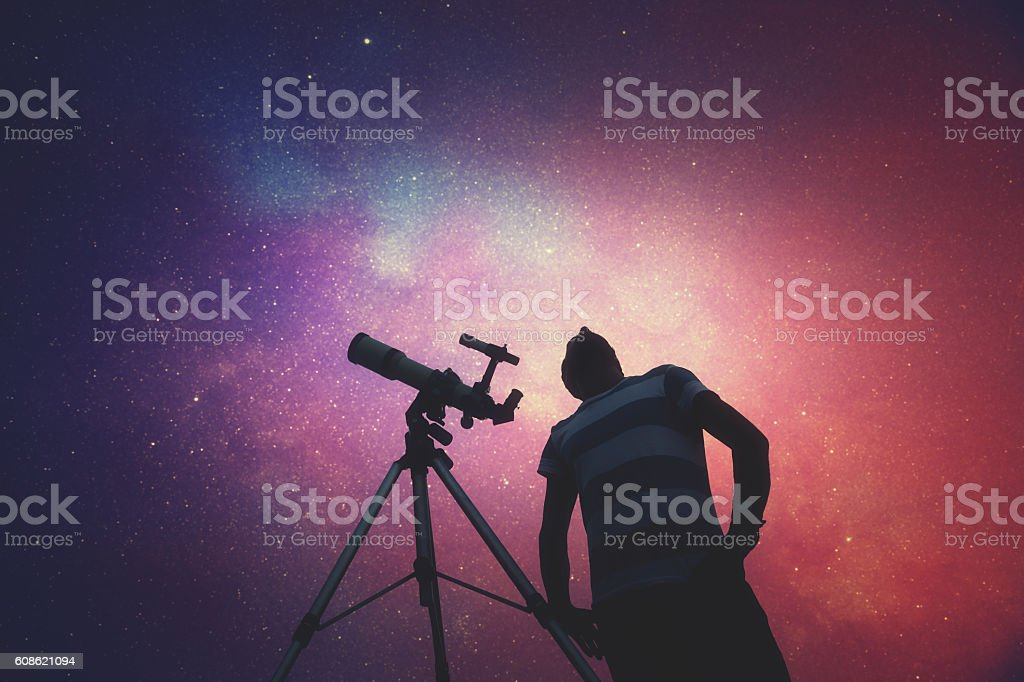 Man looking at the stars with telescope beside him. stock photo