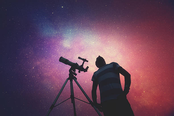 man looking at the stars with telescope beside him. - astronomie photos et images de collection