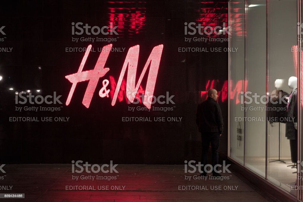 Man looking at the window of an H&M store in the Serbian capital city, a giant logo of H&M can be seen in background stock photo