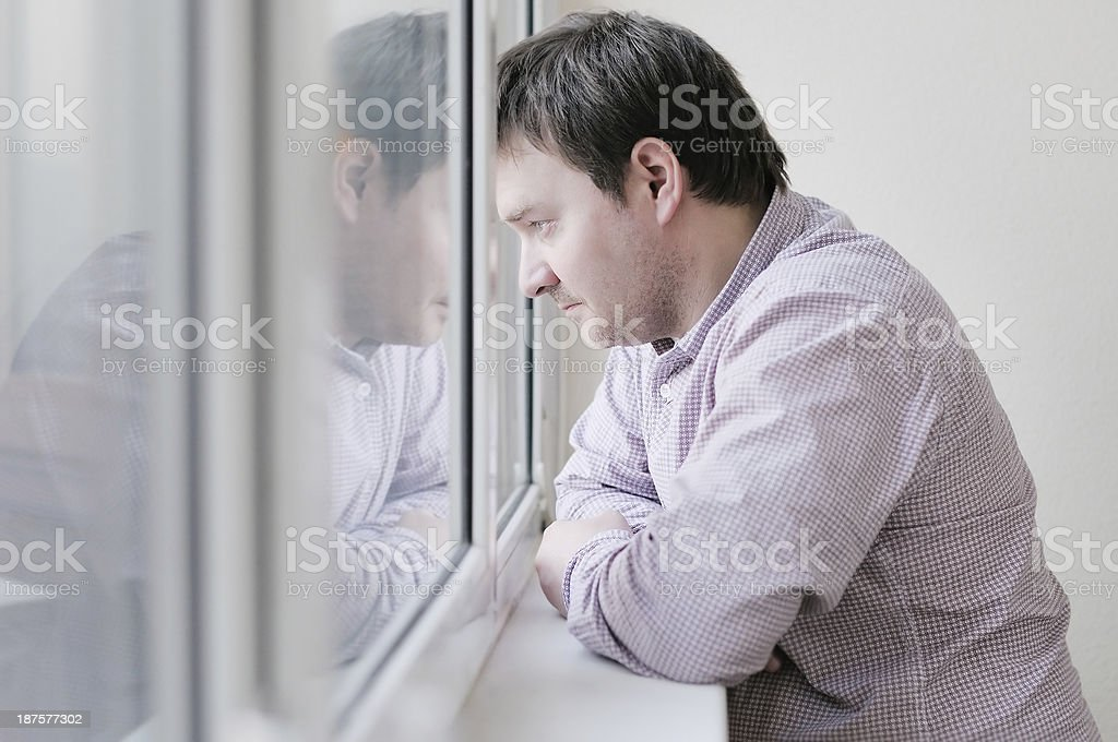 Man looking at the window stock photo