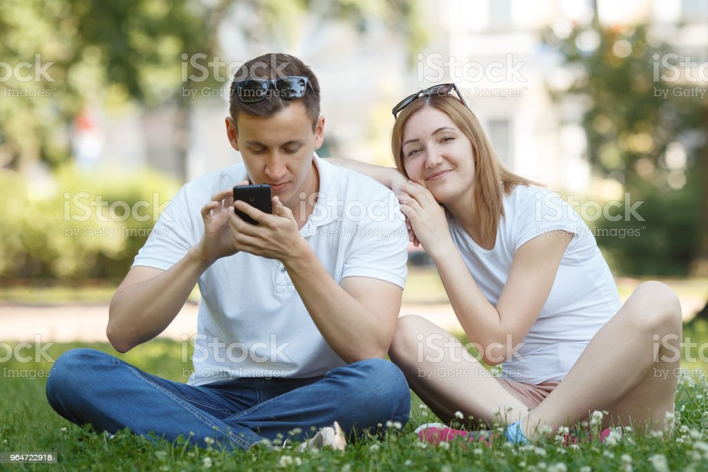 Man looking at their mobile phone while on a date royalty-free stock photo