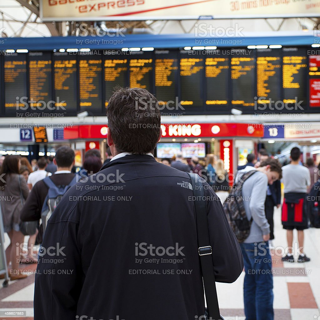 Man looking at timetable in Victoria Station, London stock photo