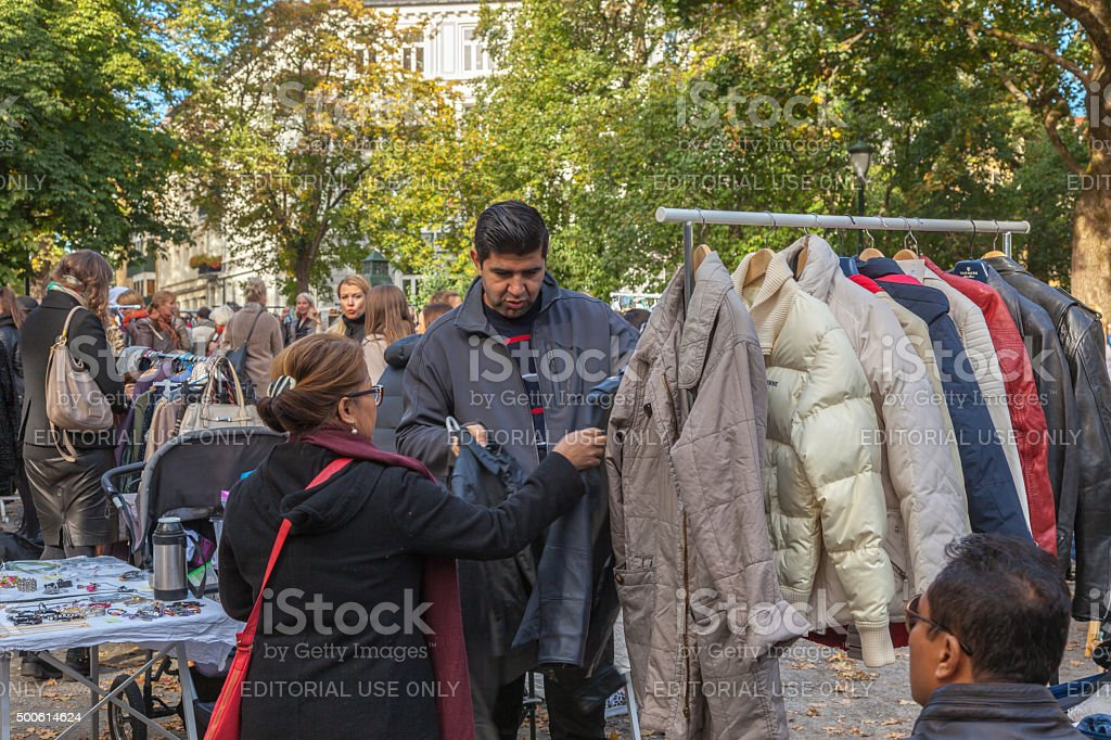 Man looking at used clothing and bags at outdoor market. stock photo