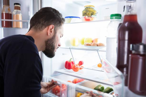 man tittar på grönsaker i kylskåp - cravings bildbanksfoton och bilder