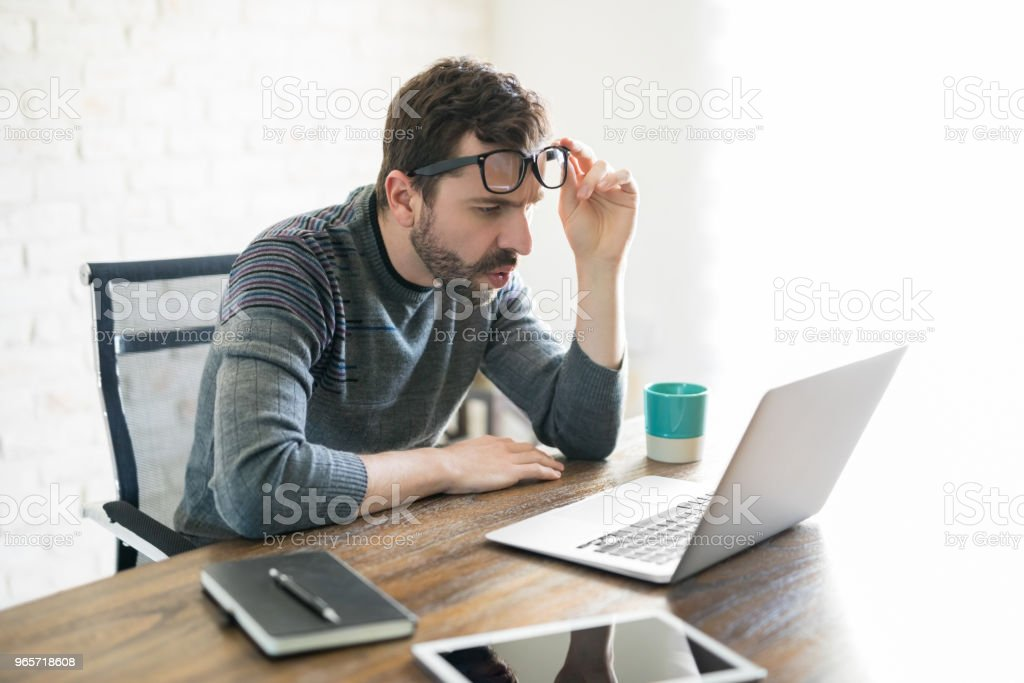 Man looking closely at his laptop - Royalty-free 30-39 Years Stock Photo