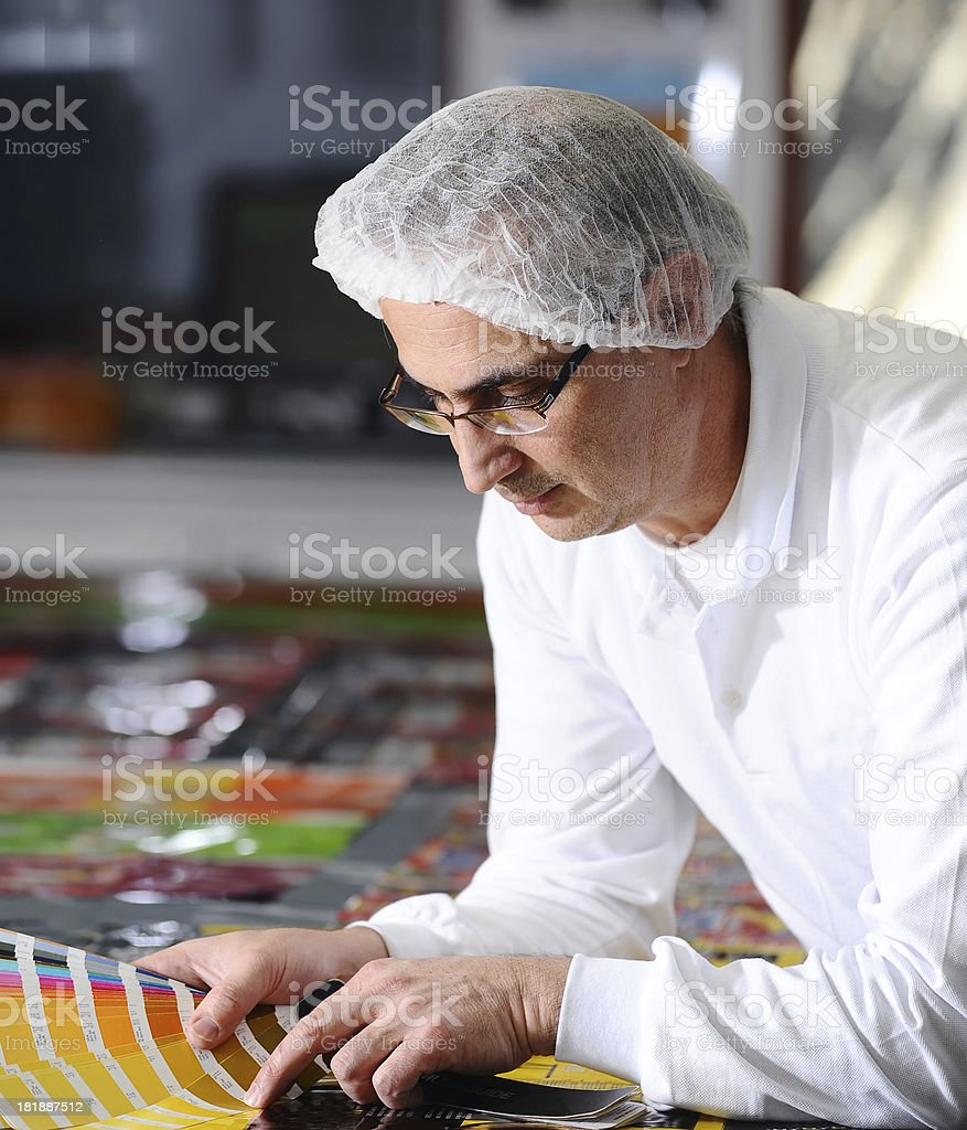 Man looking color card in printing room stock photo