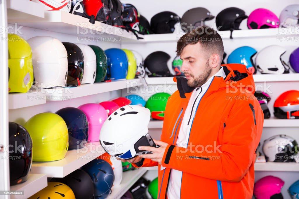 man looking for skiing helmet stock photo