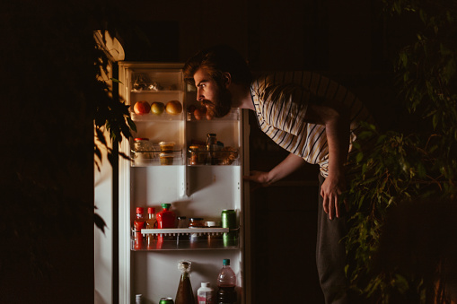 Man looking for snacks in the refrigerator late night