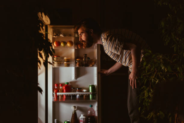 Man looking for snacks in the refrigerator late night stock photo