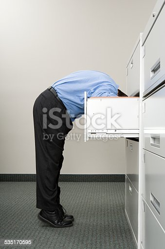 535191355istockphoto Man looking in filing cabinet 535170595