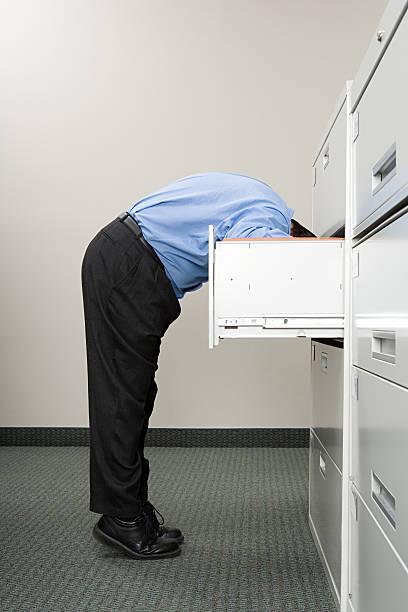 man looking in filing cabinet - looking inside inside cabinet bildbanksfoton och bilder