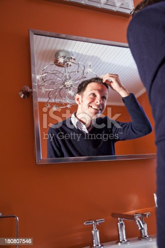 istock Man looking in mirror 180807546