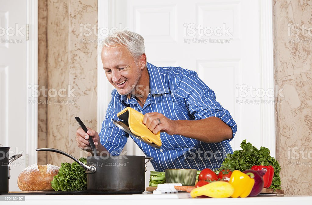 Man looking in pot on stove royalty-free stock photo