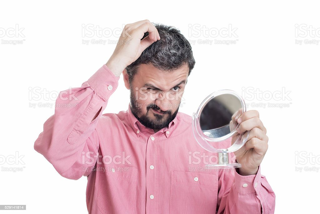 Man looking in the mirror at the first grey hair stock photo