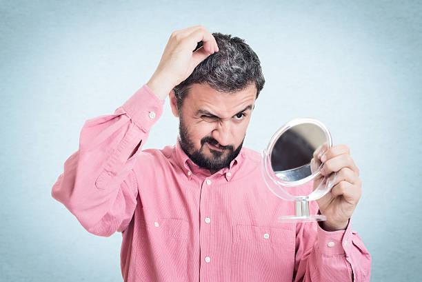 man looking in the mirror at the first grey hair - kır saç stok fotoğraflar ve resimler