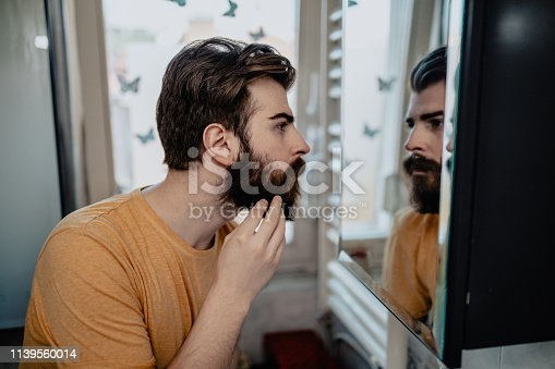1134770826 istock photo Man looking in the mirror in the bathroom 1139560014