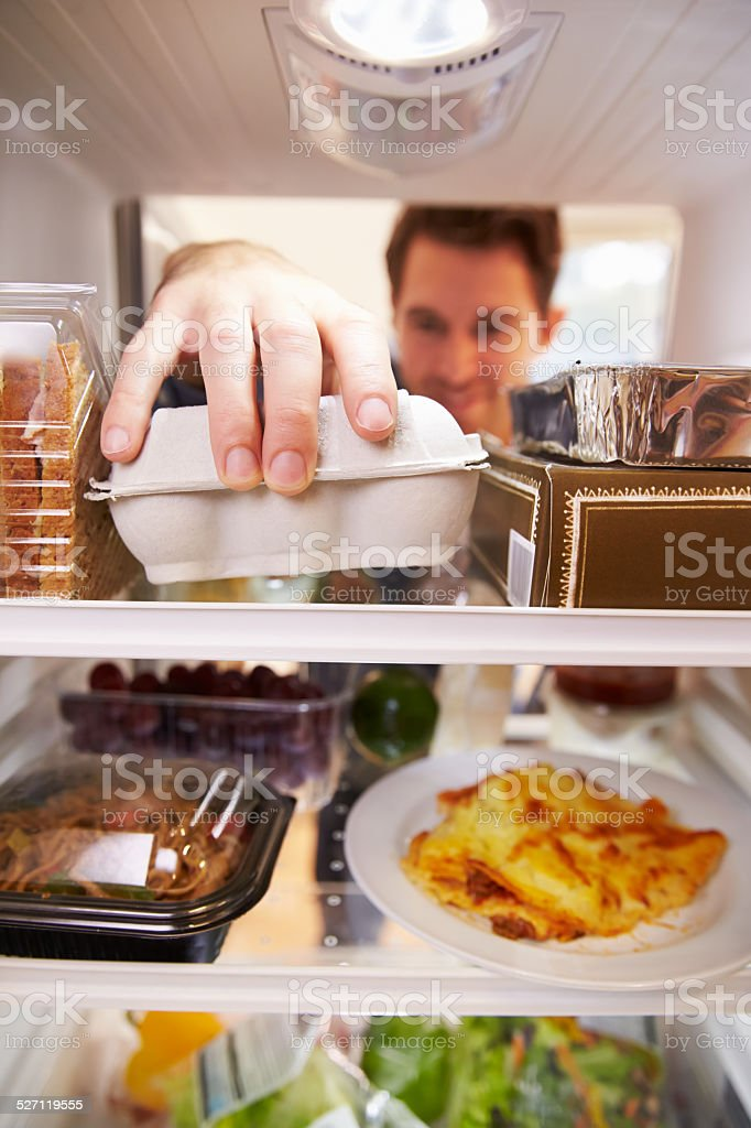 Man Looking Inside Fridge Filled With Food And Choosing Eggs stock photo