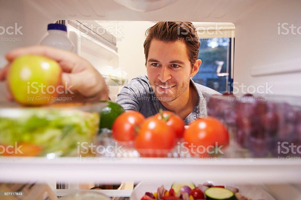 Man Looking Inside Fridge Full Of Food And Choosing Apple stock photo
