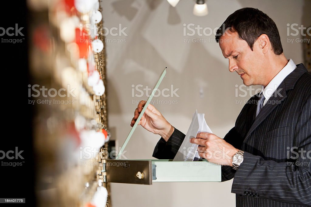 Man looking inside safety deposit box stock photo