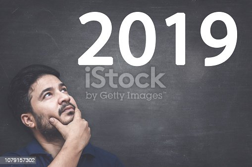1034181368 istock photo Man looking New Year 2019 Resolutions on Blackboard 1079157302