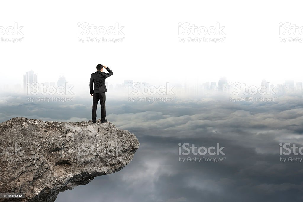 man looking on cliff with gray cloudy sky cityscape  background stock photo