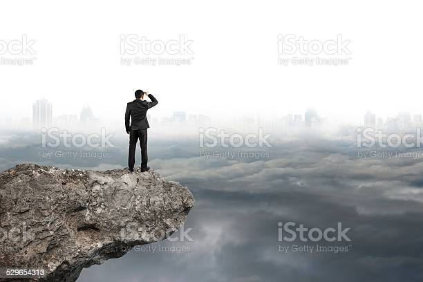 Photo of man looking on cliff with gray cloudy sky cityscape  background