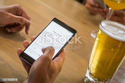 Checking menu on smart phone at the pub.