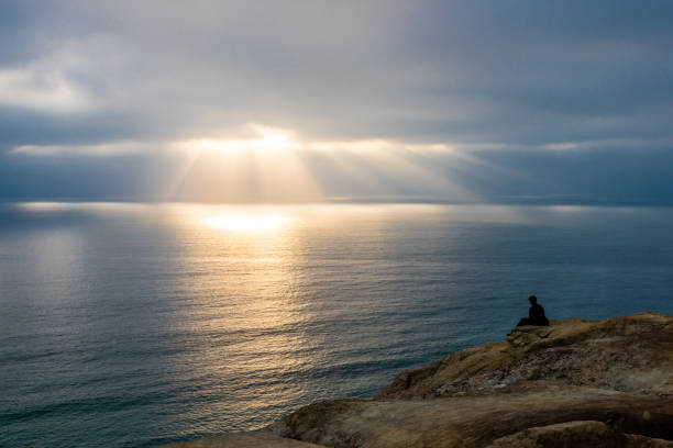 Man Looking Out at Ocean at Rays of Light stock photo
