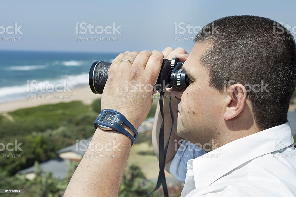 Man looking out at sea with binoculars stock photo