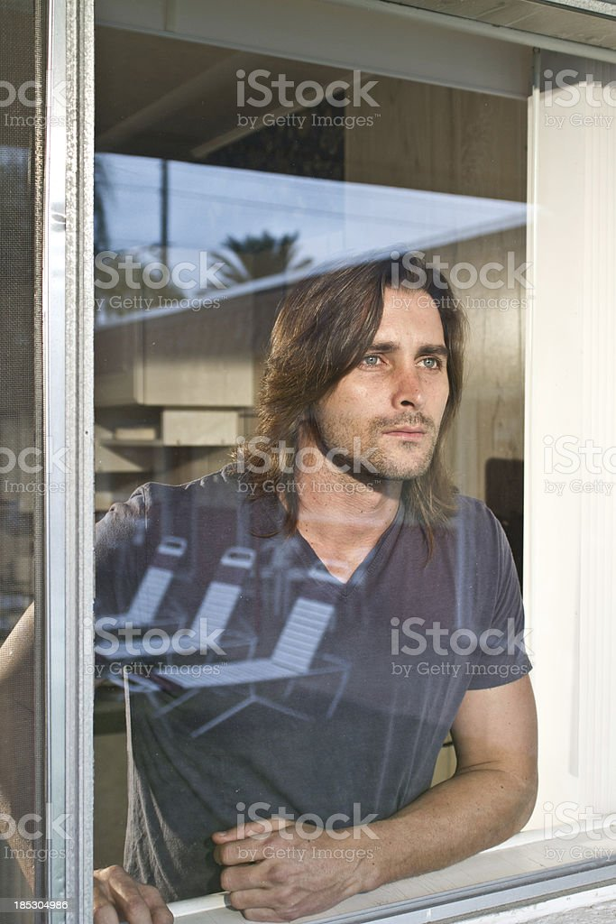 Man looking out of window royalty-free stock photo