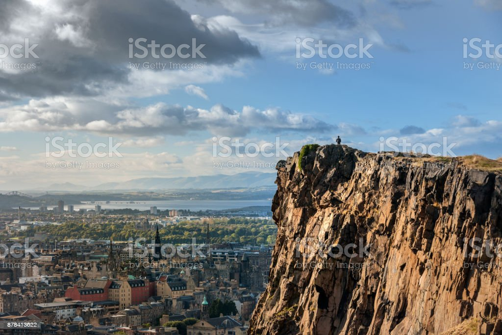 Man looking out over the City of Edinburgh from Salisbury Crags in Holyrood Park at sunset stock photo