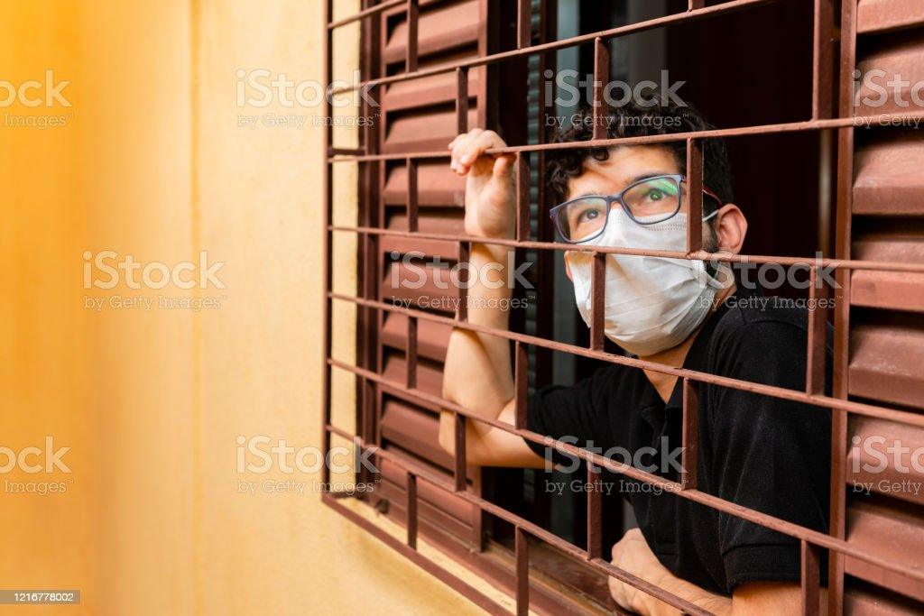 Man looking out the window during social isolation Man looking out the window during social isolation. Adult Stock Photo