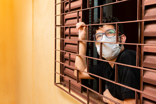 Man Looking Out The Window During Social Isolation Stock Photo - Download Image Now