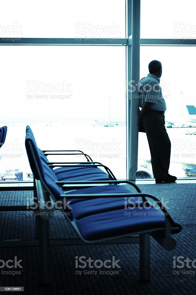 Man Looking Out Window and Waiting in Airport Terminal royalty-free stock photo