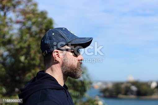 A man with sunglasses and a cap looking at the view