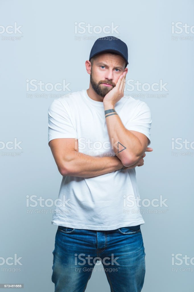 Man looking sad Portrait of man with beard staring at camera with hand on chin Adult Stock Photo