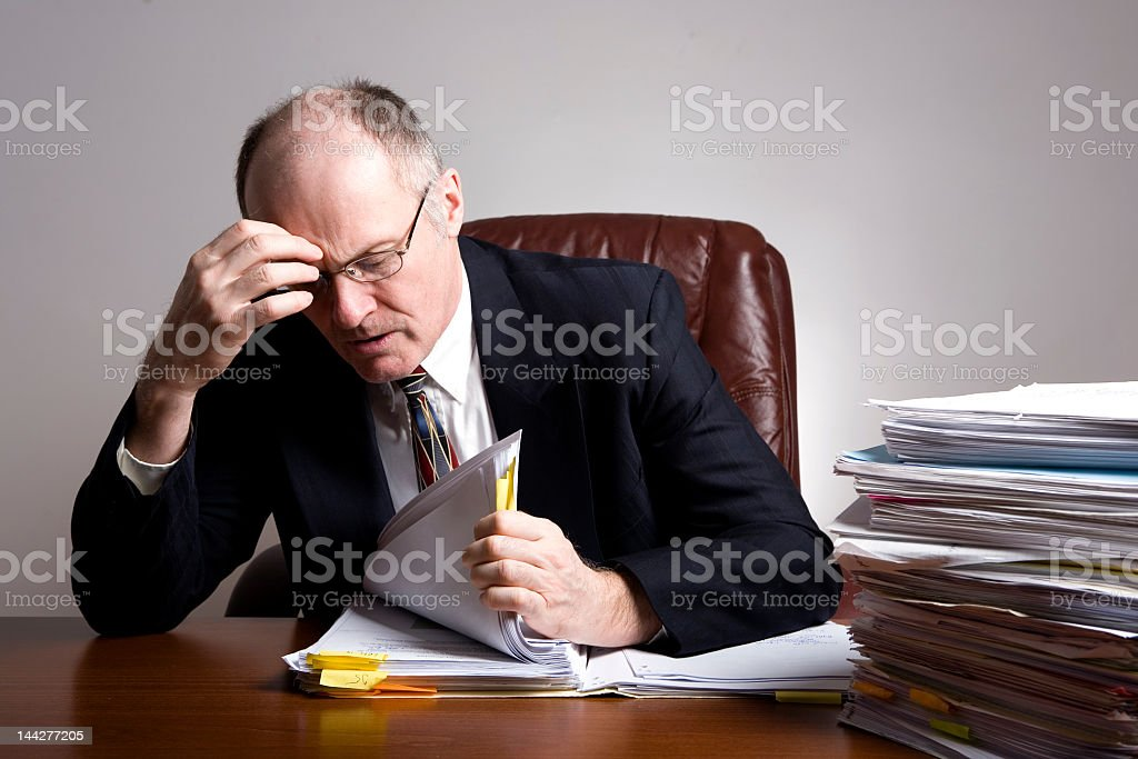 Man looking stressed at his desk surrounded by papers royalty-free stock photo